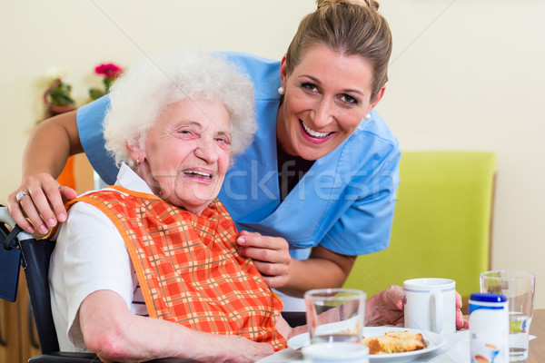 Nurse with senior woman helping with meal Stock photo © Kzenon