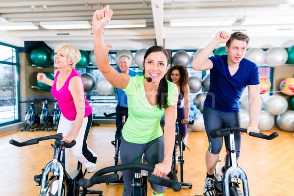 Csoport férfiak nők fitnessz biciklik tornaterem Stock fotó © Kzenon