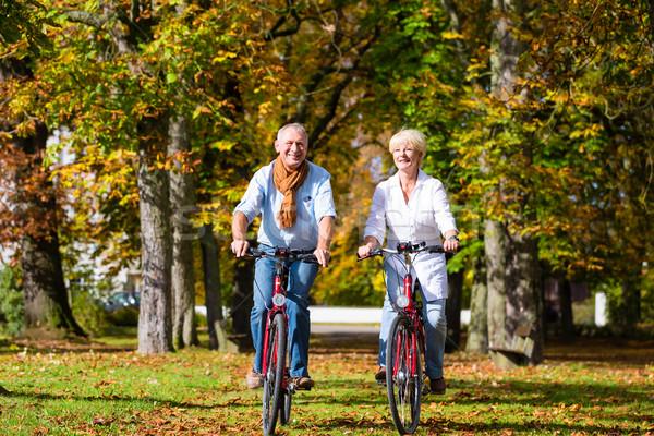 Idősek biciklik turné park idős pár férfi Stock fotó © Kzenon