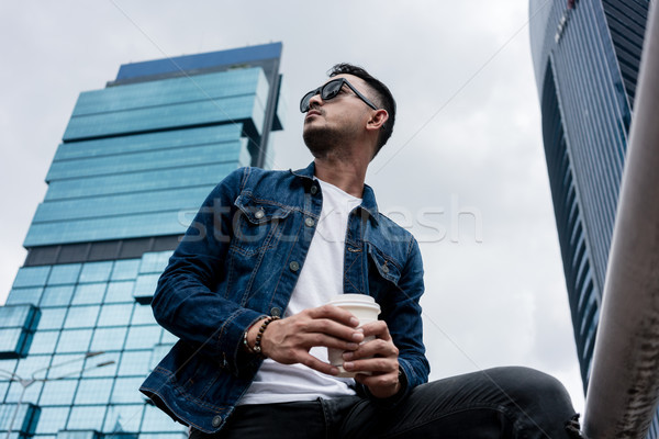 Young man wearing blue denim jacket while daydreaming outdoors i Stock photo © Kzenon