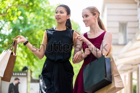 Two beautiful women looking for fashion boutiques during shoppin Stock photo © Kzenon