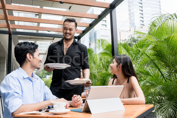 Stock photo: Cheerful waiter bringing two plates of food to the table of a young couple
