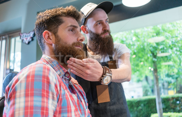 Bearded young man thinking of a trendy change of look in the hair salon Stock photo © Kzenon