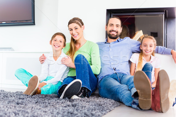 Família sessão sala de estar piso lareira família feliz Foto stock © Kzenon