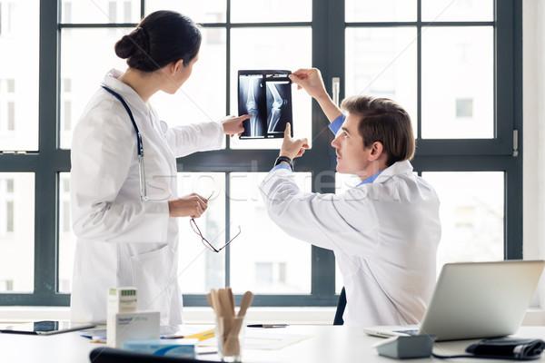 Experienced orthopedist helping his colleague Stock photo © Kzenon