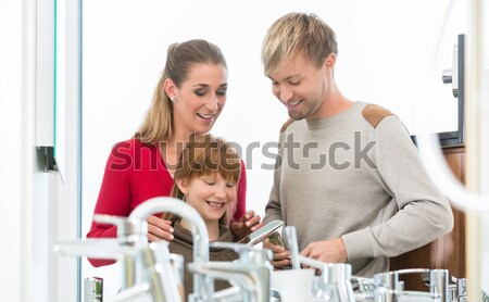 Happy mother looking with her daughter at two faucets Stock photo © Kzenon