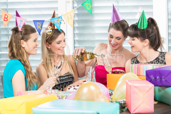 Cheerful woman holding a gift box during a surprise birthday party Stock photo © Kzenon