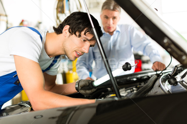 Mature man and mechanic looking at car engine  Stock photo © Kzenon
