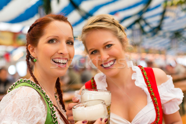 Women with traditional Bavarian clothes or dirndl in beer tent Stock photo © Kzenon