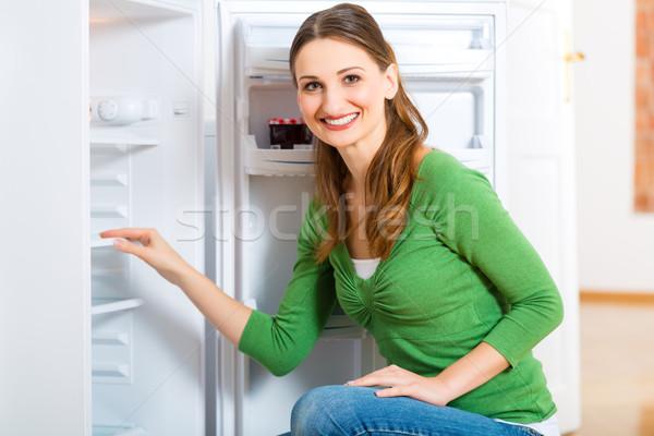 Huishoudster koelkast jonge vrouw voorjaar deur jonge Stockfoto © Kzenon