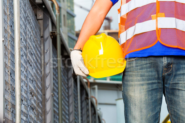 Worker on construction site with helmet or hard hat Stock photo © Kzenon