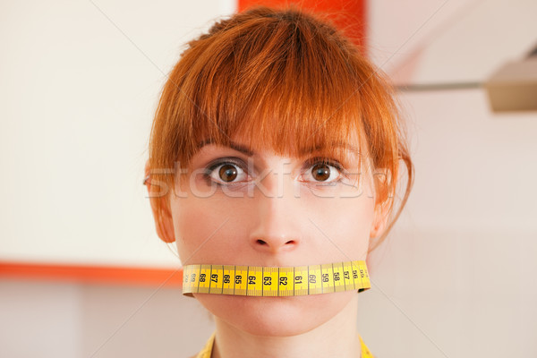 Stock photo: Woman gagged by a tape measure