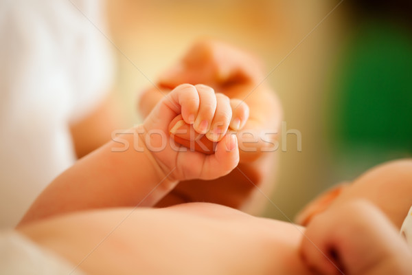 Baby gripping hand of mother Stock photo © Kzenon