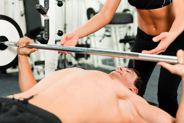man in gym exercising with barbell Stock photo © Kzenon