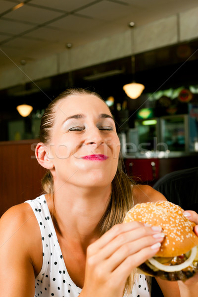 Vrouw restaurant eten hamburger gelukkig fastfood restaurant Stockfoto © Kzenon