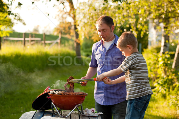Family having barbecue in their garden Stock photo © Kzenon