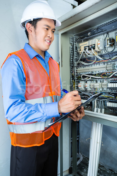 Asian Electrician at panel on construction site Stock photo © Kzenon