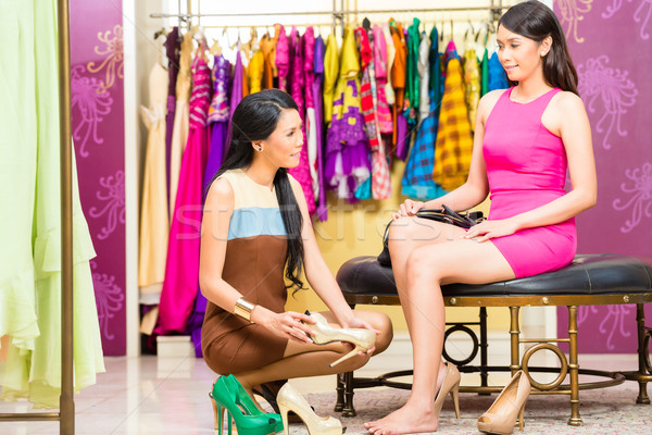 Asian sales lady in shop offering shoes Stock photo © Kzenon