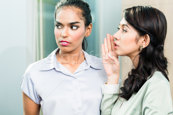Gossip in the office, woman whispering in ear Stock photo © Kzenon