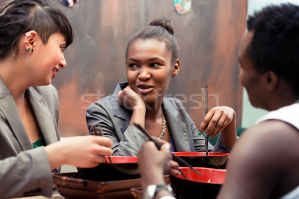Friends eating noodle soup in Japanese Restaurant Stock photo © Kzenon