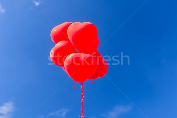 Piros szív alakú hélium léggömbök repülés Stock fotó © Kzenon