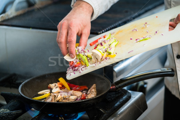 Chef putting ingredients to pan in restaurant kitchen Stock photo © Kzenon
