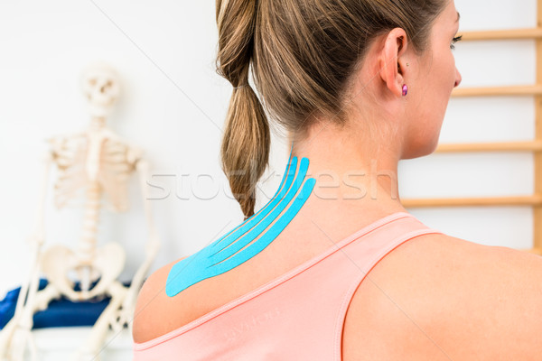 Woman from behind with Kinesio tape on shoulder in physiotherapy Stock photo © Kzenon