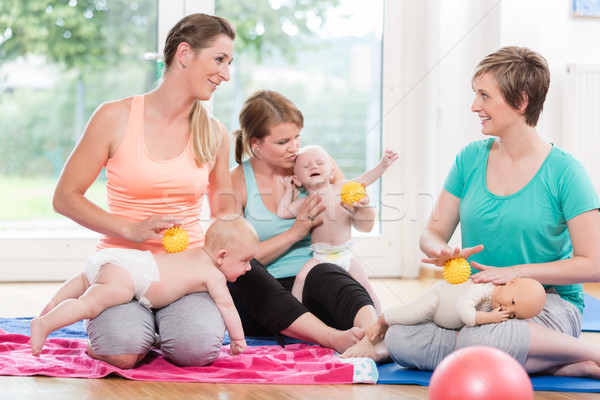 Young women practicing massage for their babies in mother-child  Stock photo © Kzenon