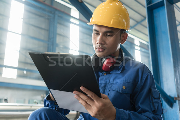 Asian worker writing observations about manufacturing Stock photo © Kzenon