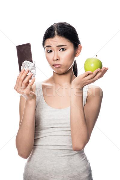 Woman eating a fresh apple while looking at chocolate Stock photo © Kzenon