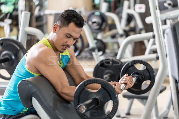 Young man exercising bicep curls with the E-Z barbell Stock photo © Kzenon
