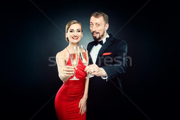 Elegant woman and man clinking glasses on glamourous party Stock photo © Kzenon