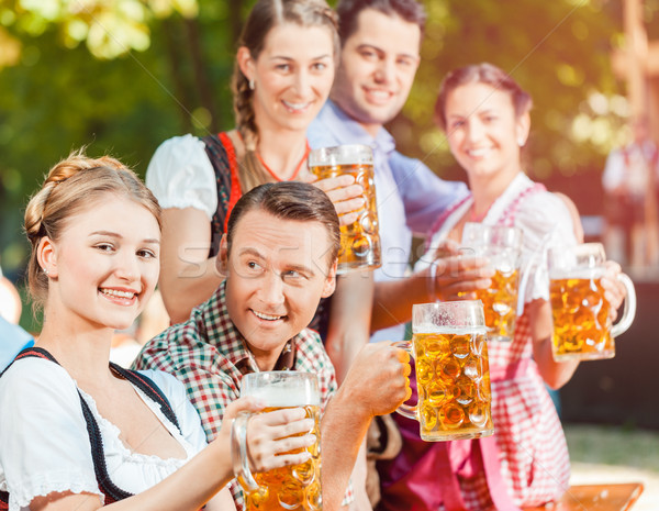 In Beer garden - friends drinking beer in Bavaria on Oktoberfest Stock photo © Kzenon