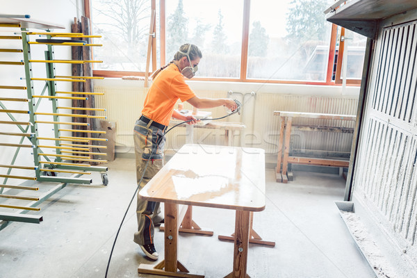Stock photo: Woman carpenter spraying varnish on a table she works on
