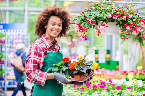 Portrait of a cheerful young woman working as florist in a modern flower shop Stock photo © Kzenon