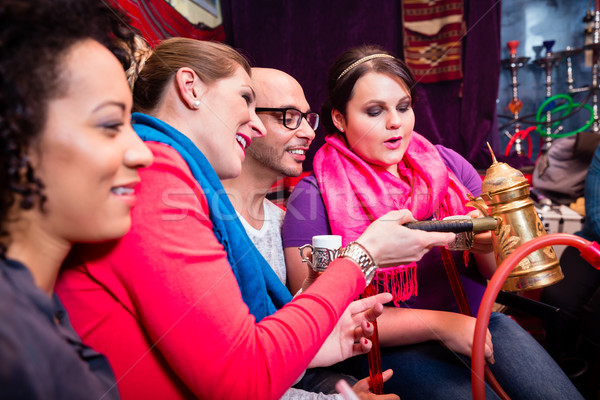 Group of friends smoking hookah and drinking coffee in shisha lounge Stock photo © Kzenon