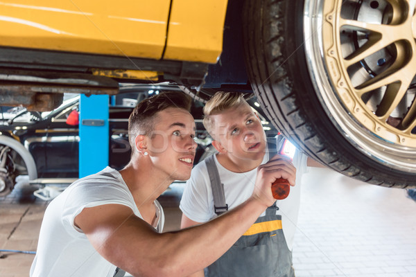 Two dedicated auto mechanics tuning a car through the modification of the rims Stock photo © Kzenon