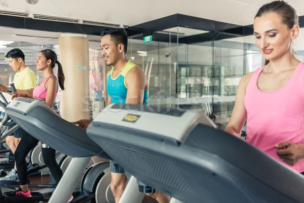 Fit active woman running on treadmill in a trendy fitness club Stock photo © Kzenon
