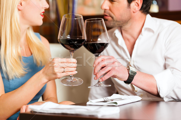 Attractive couple drinking red wine in restaurant or bar Stock photo © Kzenon