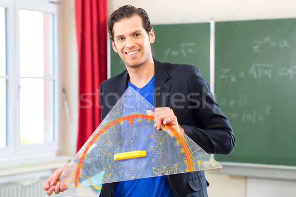 Teacher  with triangle in front of a school class Stock photo © Kzenon