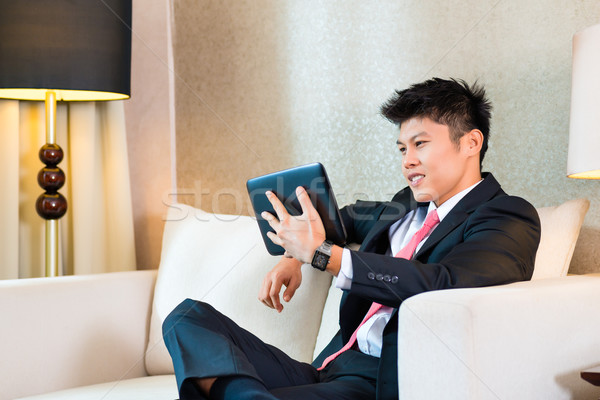 Empresário asiático quarto de hotel trabalhando comprimido computador Foto stock © Kzenon