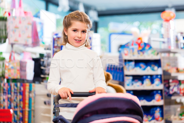 Little girl playing with baby doll carriage in toy store Stock photo © Kzenon