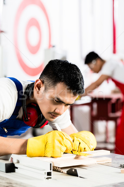 Stock photo: Diligent worker in factory working on wood
