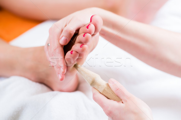 Women at reflexology having foot massaged Stock photo © Kzenon