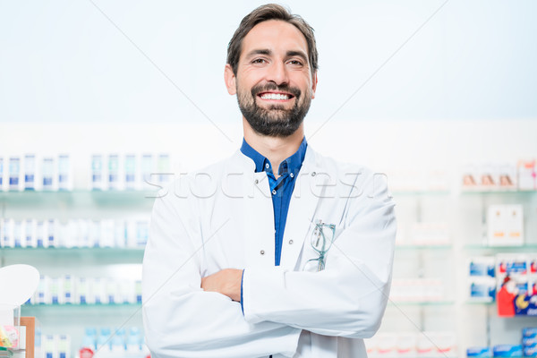 Apothecary in pharmacy standing at shelf with drugs Stock photo © Kzenon