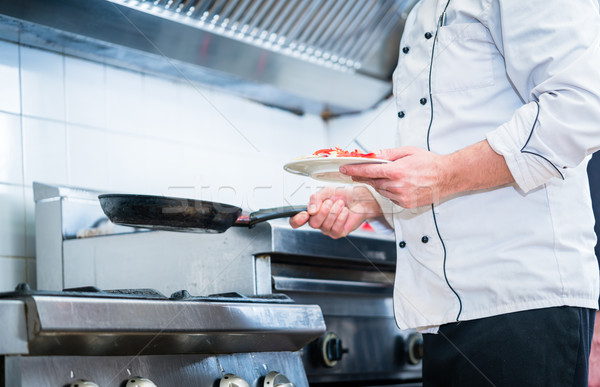 Chef with pan in restaurant kitchen Stock photo © Kzenon