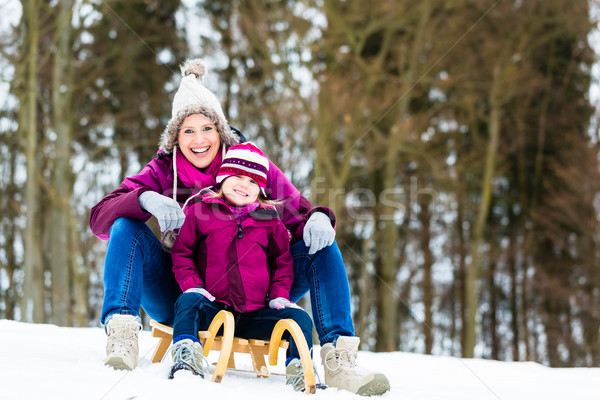 Woman and daughter on sled in winter Stock photo © Kzenon