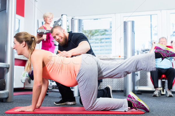 Pregnant woman working out with personal trainer at the gym Stock photo © Kzenon