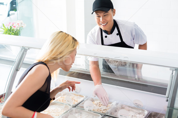 Friendly smiling deli worker helping a customer Stock photo © Kzenon