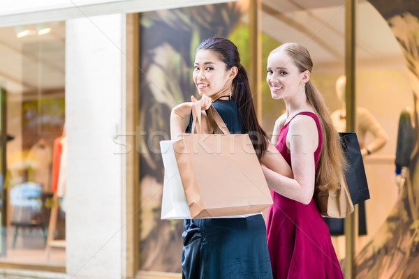 Two happy women looking at camera while carrying paper bags duri Stock photo © Kzenon
